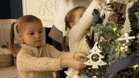 Madre y niños que adornan el árbol de Navidad en sala de estar hermosa de la familia con la chimenea almacen de metraje de vídeo