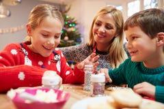Madre y niños que adornan las galletas de la Navidad juntas Foto de archivo