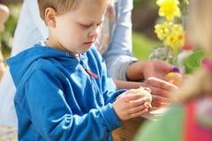 Madre y niños que adornan los huevos de Pascua Imágenes de archivo libres de regalías