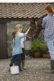 Madre y niños que alimentan el caballo fuera del establo Fotos de archivo libres de regalías