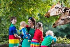 Madre y niños que alimentan la jirafa en el parque zoológico Imagen de archivo