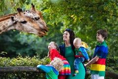 Madre y niños que alimentan la jirafa en el parque zoológico Imagenes de archivo
