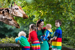 Madre y niños que alimentan la jirafa en el parque zoológico Imágenes de archivo libres de regalías