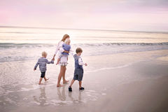 Madre y niños que caminan a lo largo de la playa del océano en la puesta del sol Imagen de archivo
