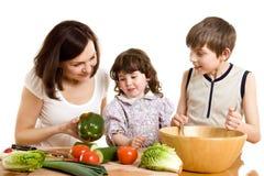 Madre y niños que cocinan en la cocina Imágenes de archivo libres de regalías