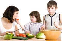 Madre y niños que cocinan en la cocina Imagen de archivo libre de regalías