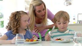 Madre y niños que comen la comida en casa junto metrajes
