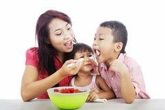 Madre y niños que comen la ensalada de fruta Imagen de archivo libre de regalías