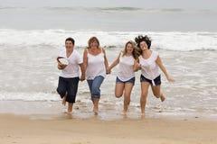 Madre y niños que corren en la playa Imagen de archivo