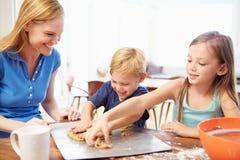 Madre y niños que cuecen las galletas juntas en casa Fotografía de archivo