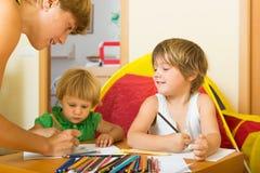 Madre y niños que dibujan con los lápices Foto de archivo