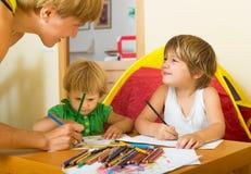 Madre y niños que dibujan con los lápices Imágenes de archivo libres de regalías