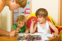 Madre y niños que dibujan con los lápices Foto de archivo libre de regalías