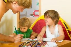 Madre y niños que dibujan con los lápices Fotos de archivo