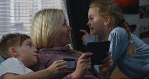 Madre y niños que hacen compras en línea almacen de video