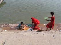 Madre y niños que hacen el lavadero Assi Ghat Varanasi India imagenes de archivo