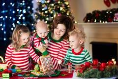 Madre y niños que hacen la casa del pan del jengibre en la Navidad Fotos de archivo libres de regalías