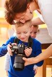 Madre y niños que juegan con la cámara que toma la foto Fotos de archivo