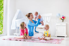 Madre y niños que juegan en dormitorio Foto de archivo