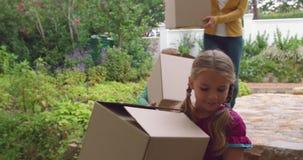 Madre y niños que llevan las cajas de cartón hacia 4k casero metrajes