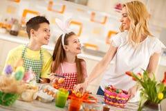 Madre y niños que preparan la cesta de Pascua con los huevos Fotos de archivo