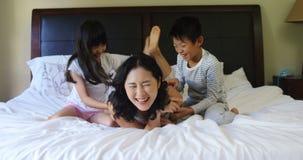 Madre y niños que se divierten en cama en el dormitorio 4k almacen de metraje de vídeo