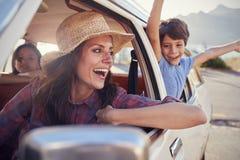 Madre y niños que se relajan en coche durante viaje por carretera imagenes de archivo