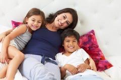 Madre y niños que se relajan en pijamas que llevan de la cama Imagenes de archivo