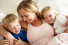 Madre y niños que se relajan junto en cama Imagen de archivo