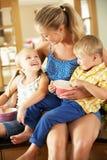 Madre y niños que se sientan en contador de cocina Imágenes de archivo libres de regalías