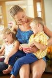 Madre y niños que se sientan en contador de cocina Imagen de archivo