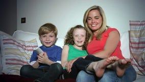 Madre y niños que se sientan en Sofa Watching TV junto metrajes