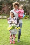 Madre y niños que sostienen la cesta de narcisos Fotos de archivo