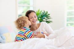 Madre y ni?o en cama Mam? y beb? en casa foto de archivo