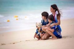 Madre y ni?o que juegan en la playa tropical Vacaciones de verano del mar de la familia Mamá y niño, niño pequeño, juego en el ag imagen de archivo