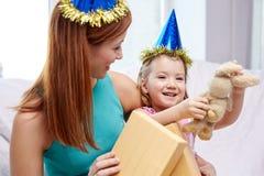 Madre y niña felices con el regalo en casa Imagenes de archivo
