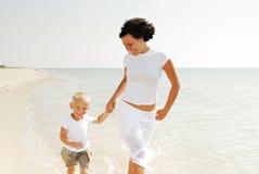 Madre y niño en la playa Imágenes de archivo libres de regalías