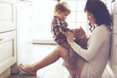 Madre y niño que juegan con el gato Fotos de archivo libres de regalías