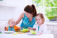Madre y niños que cocinan en una cocina blanca Imagen de archivo