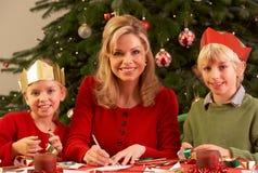 Madre y niños que hacen las tarjetas de Navidad Togethe Imágenes de archivo libres de regalías