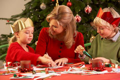 Madre y niños que hacen tarjetas de Navidad Fotos de archivo