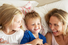 Madre y niños que se relajan junto en cama Imágenes de archivo libres de regalías