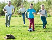 Madre y padre con dos niños que corren después de bola Foto de archivo libre de regalías