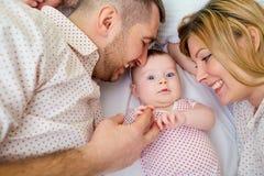 Madre y padre con la mentira sonriente del bebé imagen de archivo libre de regalías