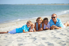 Madre y padre con tres niños en la playa Imagenes de archivo