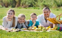 Madre y padre felices con dos adolescentes que mienten en el jardín Fotografía de archivo
