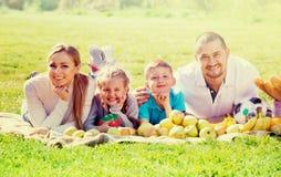 Madre y padre felices con dos adolescentes que mienten en el jardín Imagenes de archivo