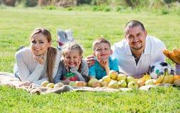 Madre y padre felices con dos adolescentes que mienten en el jardín Foto de archivo