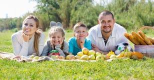 Madre y padre felices con dos adolescentes que mienten en el jardín Imágenes de archivo libres de regalías