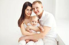 Madre y padre felices de la familia con el bebé en casa en el sitio blanco Fotografía de archivo libre de regalías